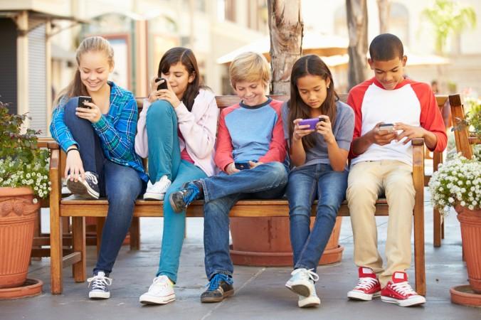 Kein seltenes Bild: Statt miteinander zu sprechen, sitzen die Kids nebeneinander und starren auf Ihre Handys. Das ist definitiv keine gelungene Kommunikation oder ein schönes Zusammentreffen zum Spielen. (#3)